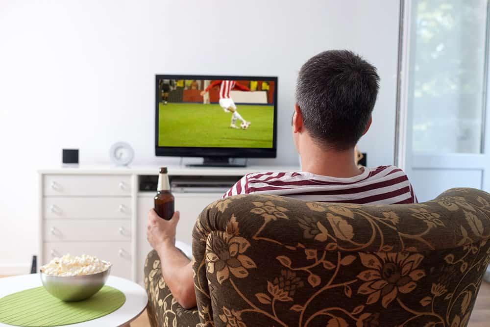 צעיר יושב בכורסת טלויזיה וצופה במשחק כדורגל